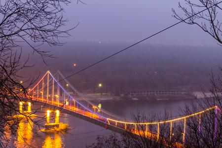 View on the pedestrian bridge across the Dnieper river at night. Kiev city, Ukraine