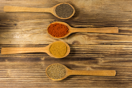 Assorted spices in wooden spoons on a table. Top view Foto de archivo