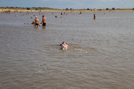 Arabat Spit, Ukraine - August 23, 2017: Unknown people bathe in the salt lake. Composition of the water in lake is the same as in the Dead Sea. Editorial