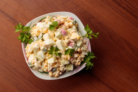 Salad with crab sticks, sweet corn, cucumber, eggs and mayonnaise on wooden table. Top view