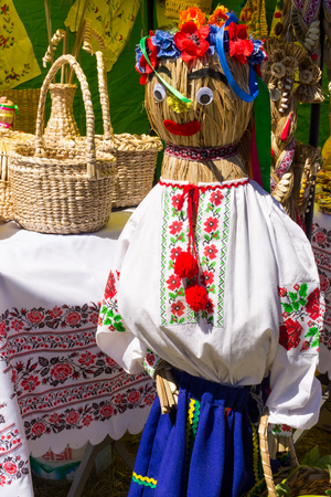 Straw dummy in traditional ukrainian clothing for decor during fair Stock Photo