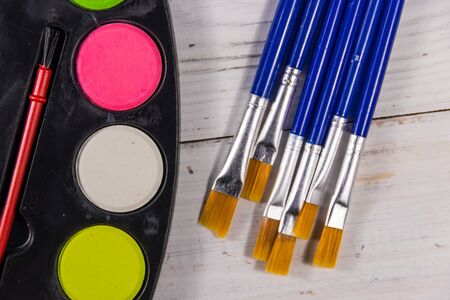 Watercolor paints and paintbrushes on white wooden desk. Top view Stock Photo