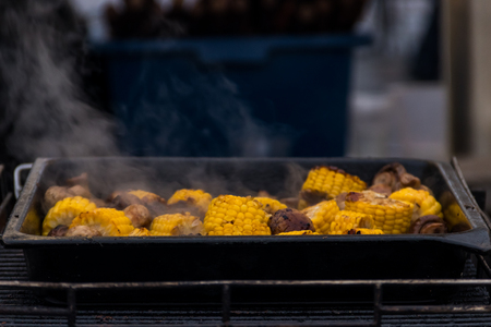 Cooking of grilled corn on the hot stove. Street food