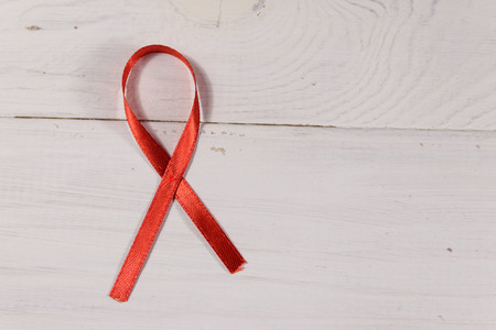 Red AIDS ribbon on white wooden background. Copy space