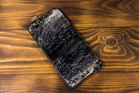 Smartphone with broken screen on wooden background
