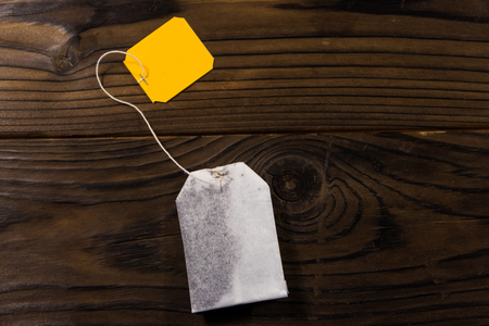 Tea bag on wooden table. Top view