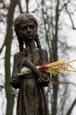 Fragment of The National Museum Holodomor victims Memorial. Sculpture of hungry young girl with ears of wheat in their hands. Kiev, Ukraine