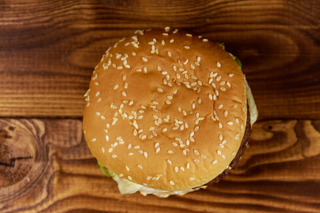 Delicious big hamburger on wooden table. Top view