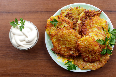 Homemade fried potato pancakes with sour cream on wooden table. Top view Foto de archivo