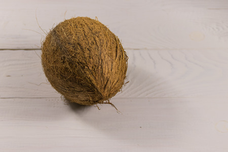 Whole coconut on white wooden table