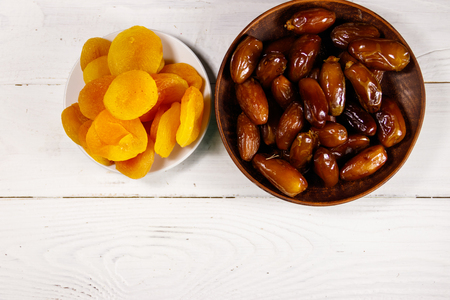 Dried apricots and dates fruit on white wooden table. Top view