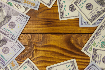 Frame of hundred dollar bills on wooden background
