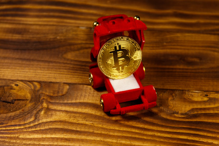 Golden souvenir coin bitcoin in car-shaped gift box for jewelry on wooden background Stock Photo