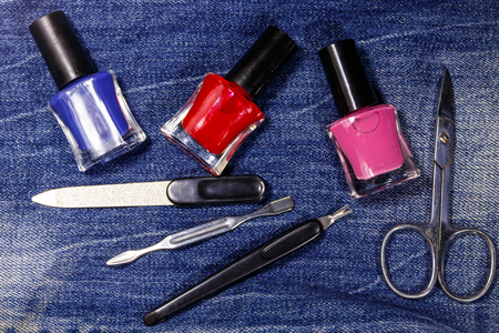 Basic set of manicure tools on jeans background. Nail and cuticle scissors, cuticle trimmer, nail file, nail polish bottles