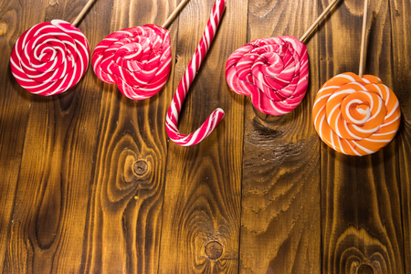 Sweet lollipops on rustic wooden background. Top view