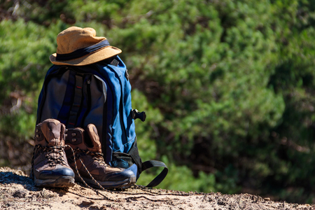 Tourist backpack, hiking boots and hat on the glade in pine forest. Hike concept