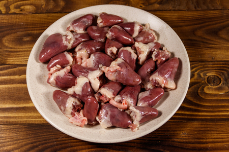 Raw chicken hearts on wooden table 스톡 콘텐츠