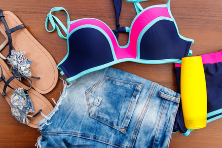 Set of beachwear on wooden background. Sunscreen, swimsuit, jean  shorts and flip-flops. Summer holiday concept Imagens