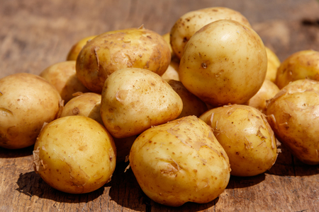 Raw new potatoes on rustic wooden table Stock Photo