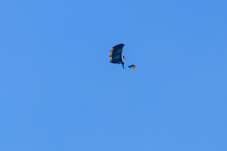 Parachutist carrying flag of Ukraine in blue clear sky Stock Photo