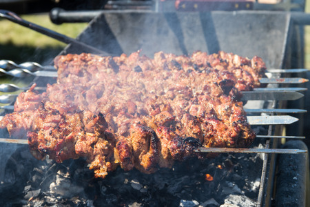 Grilled kebab cooking on metal skewer. Roasted meat cooked at barbecue.Traditional eastern dish, shish kebab. Grill on charcoal and flame, picnic, street food Stock Photo