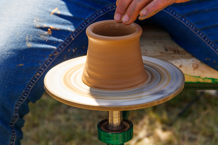 Hands of mature man making pottery on pottery wheel. Close-up Stock Photo