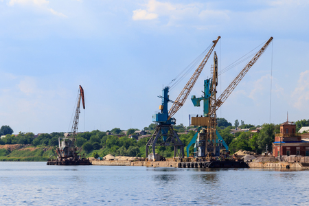 Heavy cranes in cargo port on the riverbank