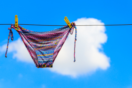 Drying female swimsuit hanging on a rope against blue sky. Summer vacation concept