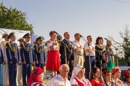 Genichesk, Ukraine - August 26, 2017: Festival of National Cultures. The organizers of the festival, the military choir and participants of the festival - representatives of different nations sing hymn of Ukraine