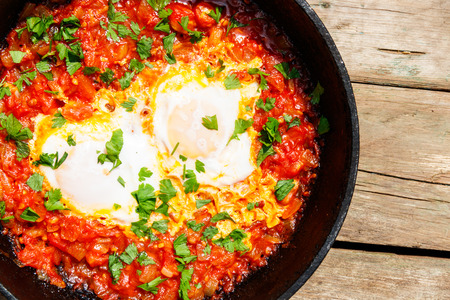 Homemade breakfast shakshuka - fried eggs, onion, bell pepper, tomatoes and parsley in cast-iron frying pan on rustic wooden table. Jewish cuisine. Top view