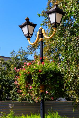 Street lantern decorated with geranium flowers in flowerpot 免版税图像
