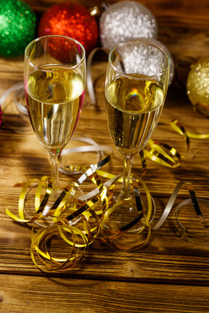 Two glasses of champagne and festive Christmas decorations on wooden table. Christmas and New Year celebration