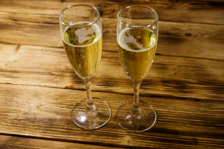 Two glasses of champagne on wooden table