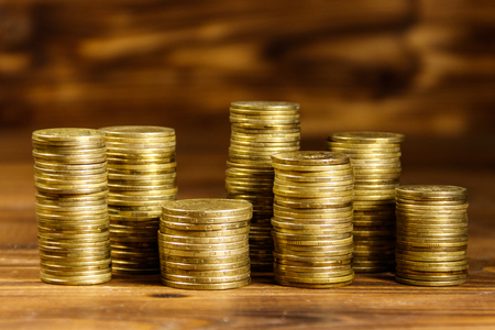 Stacks of golden coins on wooden background. Business concept Stock Photo