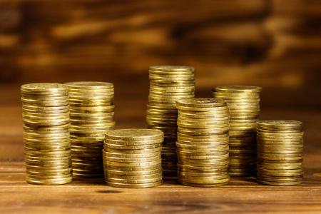 Stacks of golden coins on wooden background. Business concept Reklamní fotografie