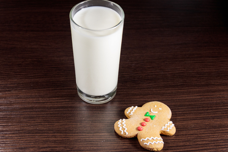 Gingerbread man and glass of milk on dark wooden table. Christmas concept Stock Photo