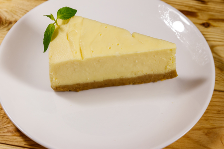 Piece of tasty sweet New York cheesecake in a white plate on wooden table 스톡 콘텐츠