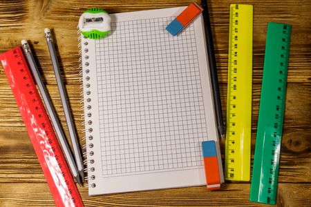 Set of school stationery supplies. Blank notepad, rulers, pencils, erasers and sharpener on wooden desk. Top view Banque d'images