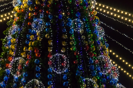 Decorated Christmas tree with multi-colored lights at night 免版税图像