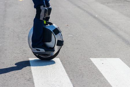 Electric unicycle. Man rides on mono wheel on zebra crossing