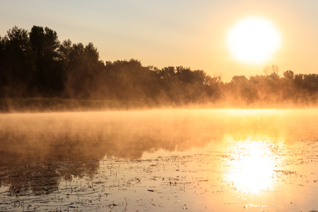 View of river in the mist at sunrise. Fog over river at morning