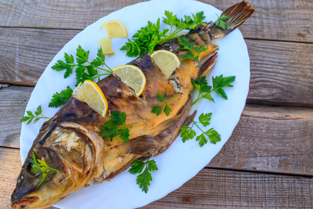 Baked carp fish with lemon and parsley on wooden table