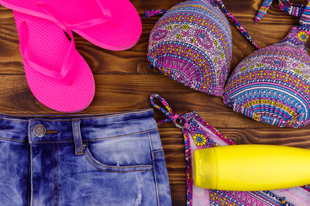 Set of beachwear on wooden background. Sunscreen, swimsuit, jean  shorts and flip-flops. Summer holiday concept 免版税图像