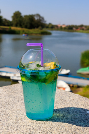 Mojito cocktail with lemon, ice and leaves of mint on a background of river