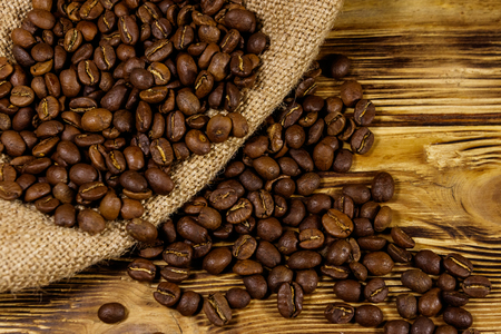 Roasted coffee beans on sackcloth on wooden table