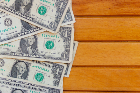 American one dollar bills on wooden background. Top view, copy space