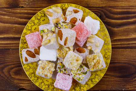 Turkish delight in a plate on wooden table Imagens