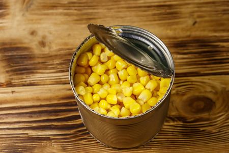 Open tin can of corn on wooden table