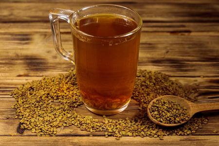 Egyptian yellow tea or Methi Dana drink and fenugreek seeds on wooden table Stock Photo