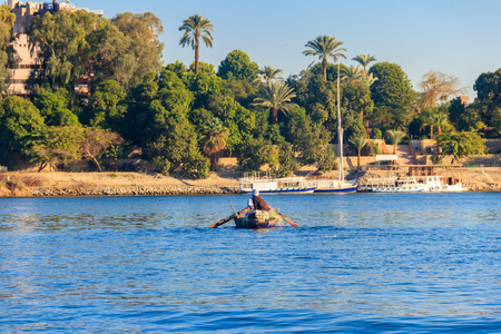 Two egyptian men fishing with fishing nets in old rowing boat on Nile river